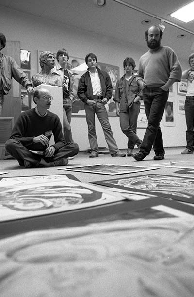 Rick Cartwright and a group of USF faculty looking over a piece of artwork on the floor