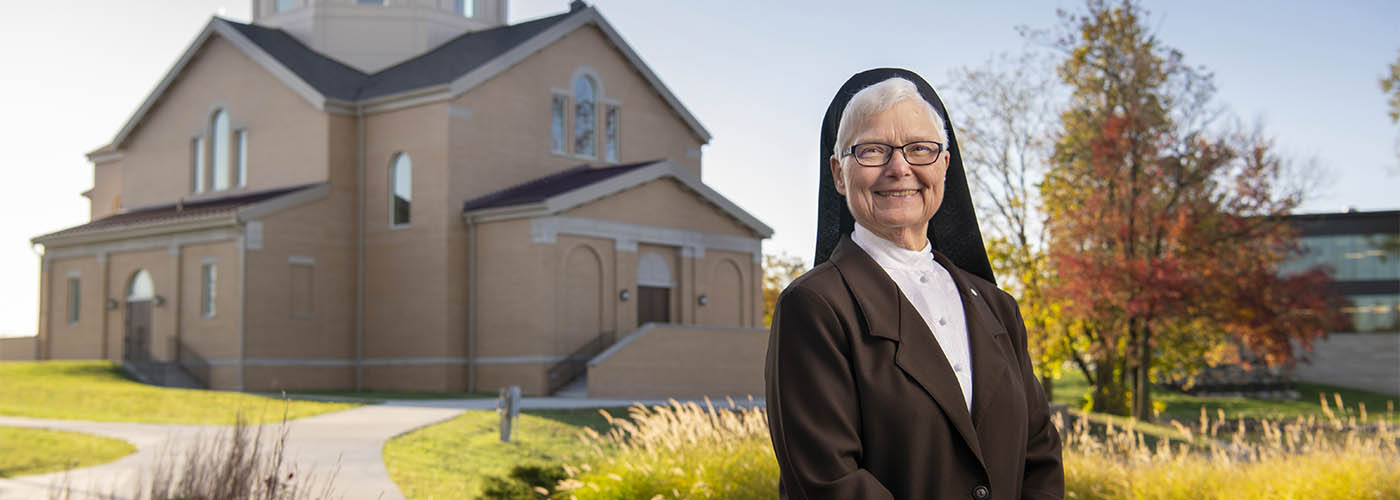 Change Agent: Sr. Elise Kriss standing in front of St. Francis Chapel